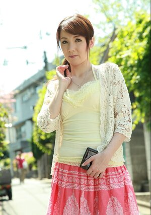 Oriental beauty with red hair seductively walks on sunny street of large city