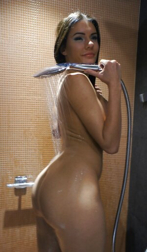 Brunette youthful dame pours water over taut tushy in the shower cabin