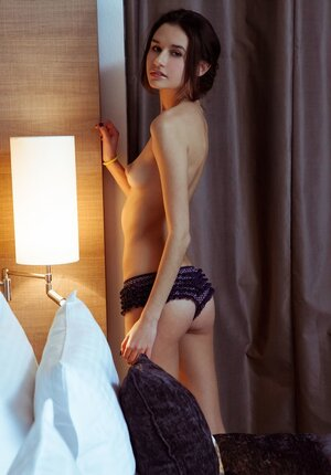 Girl enters bedroom after bathing and takes off white robe showing slender body