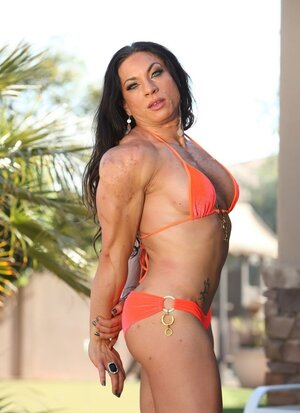Diva in orange bikini has large biceps and besides masculine chest to disport fans